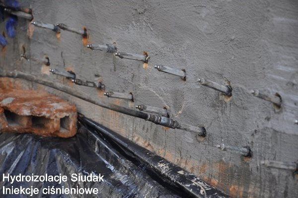Przykład wykonania iniekcji niskociśnieniowej w budynku. Realizacja: Zakopane. Materiały iniekcyjne wykorzystane do odtworzenia izolacji poziomej, oparte są na związkach krzemu do wykonywania przepony poziomej w murach zawilgoconych, szczególnie w renowacji starego budownictwa. Zalecany do uszczelniania poziomego murów metodą iniekcji niskociśnieniowej, których wilgotność osiąga wartość do 95%. Dzięki niskiej lepkości hydrofobizuje podłoże, a w wyniku reakcji chemicznej zawęża kapilary i budynek zaczyna obsychać. Cykl schnięcia może potrwać nawet do paru miesięcy od wykonania. Uzależnione jest to do wielu czynników i stopnia zawilgocenia ściany ,wilgotności powietrza, ogrzewania, itp. Jest to najbardziej skuteczna metoda bezinwazyjnego osuszania budynków stosowana w całej Europie, m.in. do renowacji zabytków i odtwarzania izolacji poziomej bez naruszania struktury ściany i w pełni ekologiczną metodą odtworzenia izolacji poziomej zarówno w starym budownictwie, jak i nowym wynikających z popełnionych błędów w fazie realizacji budynku.